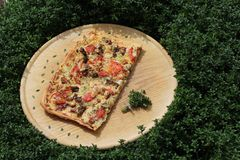 A piece of pizza on a wooden board in a thyme field royalty free stock photo