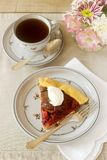 Piece of plum galett with cream and tea. Dessert. Rustic style, selective focus. Vertical Stock Photo