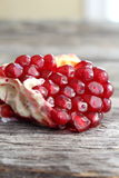 Piece of pomegranate close-up. On old wood board Stock Images