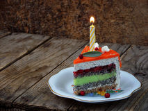 Piece of poppy cake with lime cream and strawberry jelly with a lighted candle. Happy Birthday. selective focus. Stock Photos