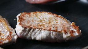 Piece of pork chop grilling on a grilling pan stock video