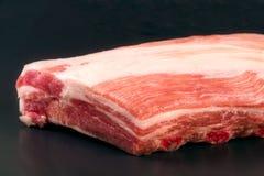 Piece of pork on a dark background Stock Photos