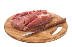 A piece of pork with a knife on a wooden board Stock Images