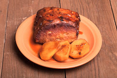 Piece of pork, peppers and potatoes in an old wooden table Royalty Free Stock Photo