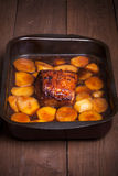Piece of pork and potatoes in the pan for roasting on an old woo Stock Photos