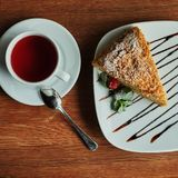 a piece of poured honey cake with chocolate topping on a plate, with cup of tea, top view royalty free stock images