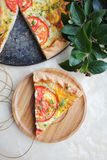 Piece of puff pastry snack pie or pizza with cottage cheese filling, tomato slices and chopped fresh dill Stock Photos