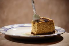 Fork stuck in part of a pumpkin cheesecake against brown background stock photography