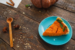 Piece of pumpkin pie on wooden table. Traditional american autumn dessert served with spoon, free space. Homemade bakery, seasonal food, kitchen concept Royalty Free Stock Image
