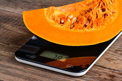 Piece of pumpkin on scales Stock Image
