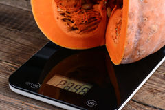 Piece of pumpkin on scales Stock Photography