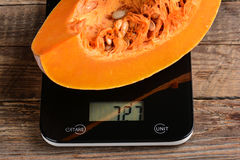 Piece of pumpkin on scales Stock Photo