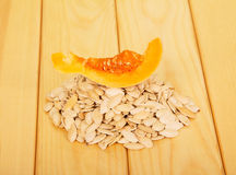 Piece of pumpkin seeds on light wooden background Royalty Free Stock Photos