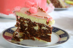 Piece of punch cake. Piece of a punch-flavoured cake with the layer cake in the background Royalty Free Stock Images