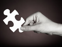 A piece of the puzzle. White puzzle piece solution in hand on a dark background royalty free stock photography