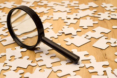 Piece Of The Puzzle. Magnifying glass looking for a piece of the puzzle Royalty Free Stock Photos