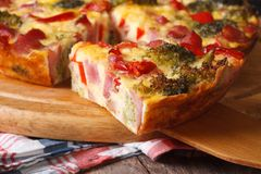 Piece of quiche with broccoli, pepper, bacon macro. Stock Photos