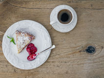 A piece of raspberry cheesecake and a cup of coffee on a wooden Royalty Free Stock Photography