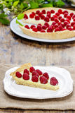 Piece of raspberry tart on wooden table Stock Photography