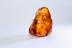 A piece of raw amber on a white table. A piece of raw yellow amber on a white table Royalty Free Stock Photos