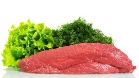 Piece of raw beef and greens isolated on white background. A piece of raw beef and greens isolated on white background Royalty Free Stock Photography