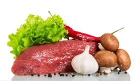 A piece of raw beef, mushrooms, lettuce, garlic and black pepper. Isolated on white background Royalty Free Stock Images