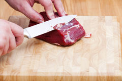 Piece of raw beef tenderloin and a kitchen knife Royalty Free Stock Images