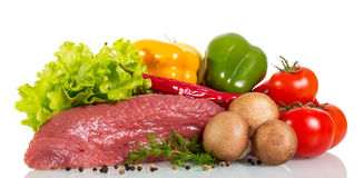 Piece of raw beef, vegetables, herbs and spices isolated. A piece of raw beef, vegetables, herbs and spices isolated on white background Stock Photo