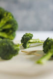 Piece of raw broccoli on white wood, close up. Small pieces of raw broccoli on white wood, Selective focus Royalty Free Stock Photo