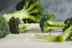 Piece of raw broccoli on white wood, close up. Small pieces of raw broccoli on white wood, Selective focus Stock Image