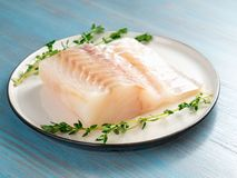Piece of raw cod fish fillet on plate on blue wooden table, side. View Stock Images