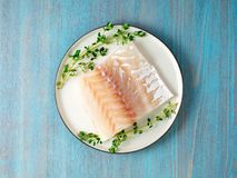 Piece of raw cod fish fillet on plate on blue wooden table, top. View Stock Image