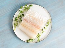 piece of raw cod fish fillet on plate on blue wooden table, top view stock photos