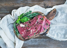 A piece of raw fresh beef (Ribeye steak) marinated in spices and. Herbs on a rustic wooden board over a kitchen towel and rough wooden desk. Top view Royalty Free Stock Photography