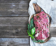 A piece of raw fresh beef (Ribeye steak) marinated in spices and. Herbs on a rustic wooden board over a kitchen towel and rough wooden desk with a copy space Stock Photo