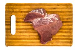 A piece of raw meat on a board isolated on white background