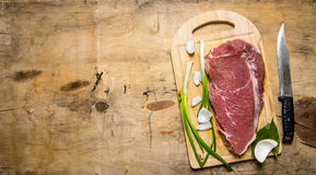 Piece of raw meat. A piece of raw meat with a butcher knife and a onion. On a wooden table. Free space for text . Top view Royalty Free Stock Photography
