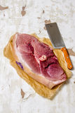 A piece of raw meat with a butcher knife on the paper. Stock Image