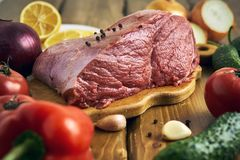 Piece of raw meat with vegetables. Big piece of fresh raw beef with vegetables on the wooden table Royalty Free Stock Photography