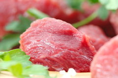 Piece of raw meat with vegetables and spices. On the table Royalty Free Stock Images