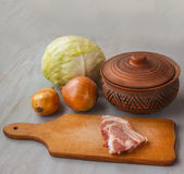 A piece of raw pork on a cutting board and vintage clay pot and Stock Image