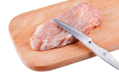Piece of raw pork and knife on wooden Board isolated. On white Stock Photos