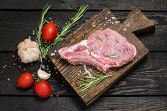 Piece of raw pork loin, vegetables, herbs and spices. Piece of raw pork loin on old cutting board, vegetables, herbs and spices on dark wooden background. Meat Royalty Free Stock Photography