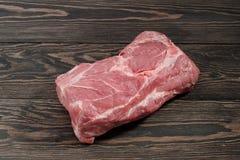 A piece of raw pork neck. Pork tenderloin on paper on a dark background. A piece of raw pork neck. Pork tenderloin on paper on a dark table Royalty Free Stock Photo