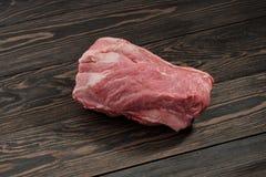 A piece of raw pork neck. Pork tenderloin on paper on a dark background. A piece of raw pork neck. Pork tenderloin on paper on a dark table Royalty Free Stock Photography