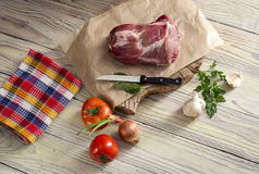 A piece of raw pork on a wooden table. Fillet of raw, fresh pork on a wooden table close-up Royalty Free Stock Images