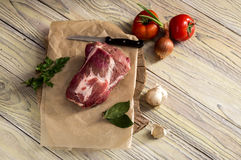 A piece of raw pork on a wooden table. Fillet of raw, fresh pork on a wooden table close-up Royalty Free Stock Photography