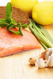 Piece of raw salmon fish with bread and vegetables Stock Images