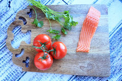 Piece of raw salmon tomatoes on the vine and a piece of cilantro Stock Image