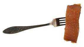 A piece of red fish on old metal fork isolated on a white backgr Stock Images